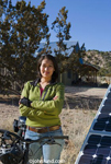 Picture of a Native American woman with a bicycle standing with arms crossed, smiling near solar panels. Behind the woman are tall pine trees and blue sky along with a building of some sort.